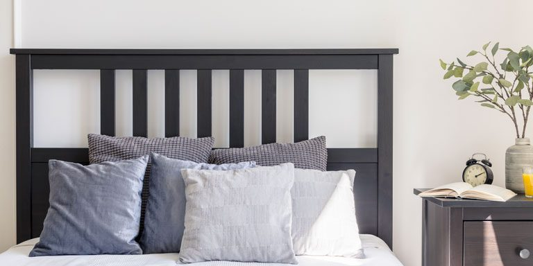 Grey and white pillows on bed with black headboard in simple bedroom interior. Real photo